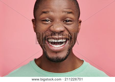 Close Up Portrait Of Positive Black Male With Dark Skin And White Perfect Teeth, Smiles Happily As F