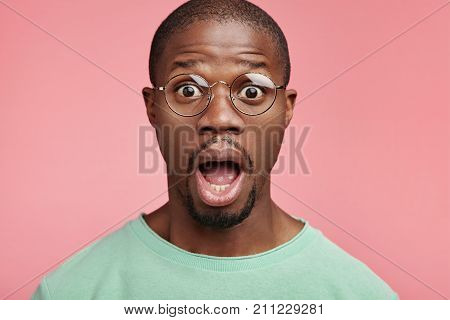 Horrified Dark Skinned Bald Man Keeps Mouth Widely Opened, Poses Agianst Pink Wall, Being Shocked Wi