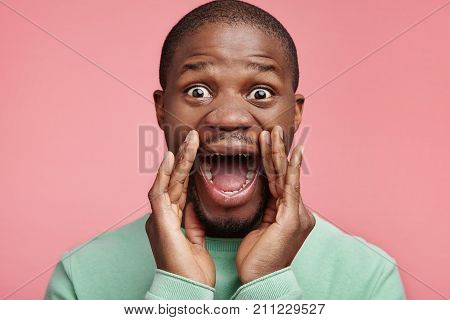 Stunned Overjoyed African American Male Student Screams With Excitement, Keeps Hands Near Mouth, Bei
