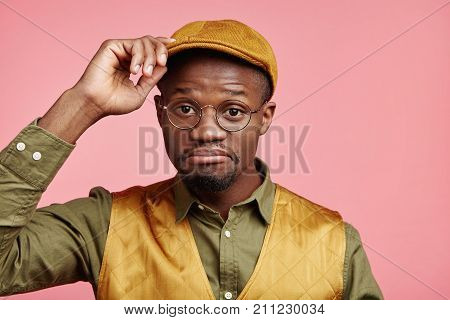 Portrait Of Hesitant Stylish Young Hipster Male With Dark Skin Wears Fashionable Cap, Shirt And Vest