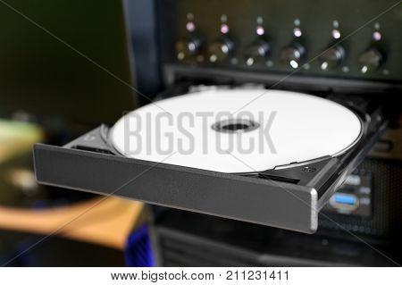 Desktop PC with open disc tray. White printable DVD disc inside.