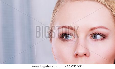 Optics contact lenses concept. Portrait of blonde woman with grey blue eyes
