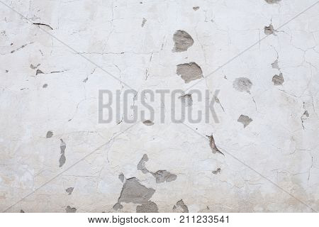 Abstract Grunge White Stucco Wall Background. Whitewash Old Rough cracked cement Texture With fallen plaster. Vintage Background With Copy Space for design