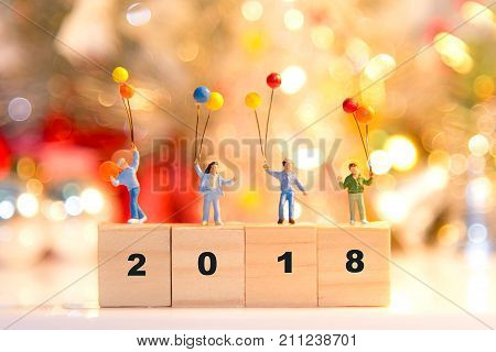 Miniature group happy family holding balloons standing on wooden 2018 with party happy new year party background.