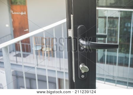 Close up door handle on opened black modern glass door that going out to balcony. (Soft focus)