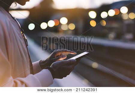Enjoying travel. Young woman waiting on station platform on background light electric moving train using smart phone in night. Tourist texting message and plan route of stop railway railroad transport bokeh