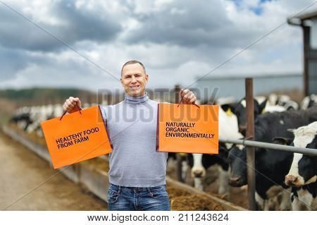 portrait of a man showing a product against background of farm cows