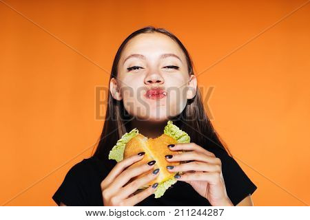 a young funny girl wants to lose weight, but eagerly eats a harmful calorie burger