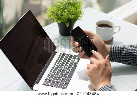 Alushta Russia - June 9 2017: Man hands holding iPhone and MacBook Pro. iPhone and MacBook was created and developed by the Apple inc.