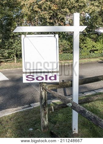 A real estate sign is placed on a corner to advertise a house was for sale and is now sold with a fence under and trees in the background.