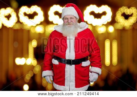 Santa Claus on blurred background. Photo of realistic Santa Claus standing on New Year lights background. Old kind Santa Claus.