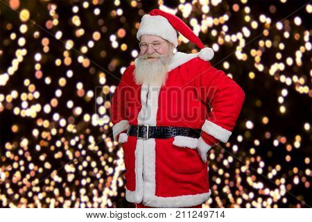 Happy Santa Claus on garlands background. Smiling bearded Santa Claus with hands on belt standing on New Year lights backgrouns. Santa Claus and miracles.