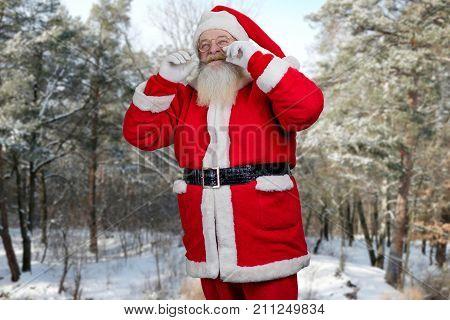 Santa Claus touching his mustache. Happy Santa Claus touching his real mustache on snowy nature background. Old Santa Claus making miracles.