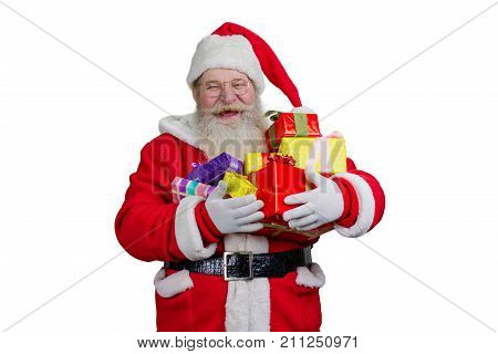 Joyful Santa Claus holding Christmas presents. Cheerful Santa Claus holding pile with gift boxes, isolated on white background.