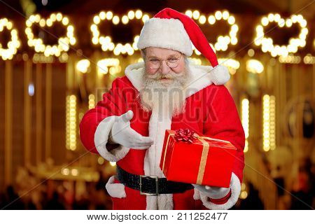 Santa Claus showing box with present. Old Santa Claus offering red box with gift standing on festive shimmering background. Santa Claus and gifts concept.