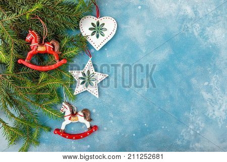 Christmas and New Year blue background with fir branches and Christmas toys - horses a star and a heart. Top view