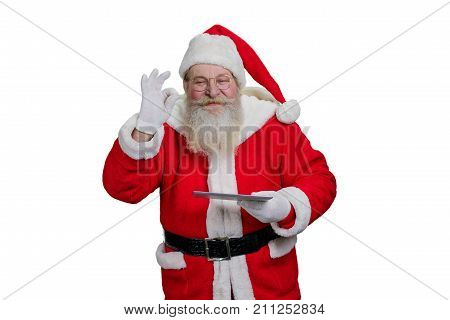 Santa Claus with digital tablet. Senior Santa Claus is realizing kids wishes making a magic on white background. Santa Claus with touch screen tablet, studio shot.