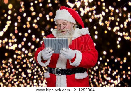 Santa Claus reading on computer tablet. Senior Santa Claus holding digital tablet and reading news, New Year lights background.