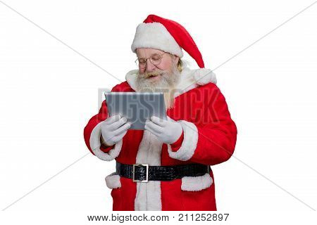 Santa Claus using pc tablet. Senior Santa Claus looking at digital tablet, isolated on white background.