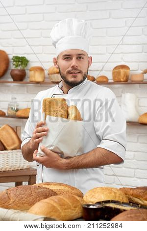 Handsome young baker posing at his store with a bunch of delicious fresh bread just from the oven profession occupation job worker salesperson seller retail cafe bakery hobby concept.
