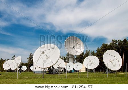 Station with space satellite dishes in the forest. Satellite space plates in the forest