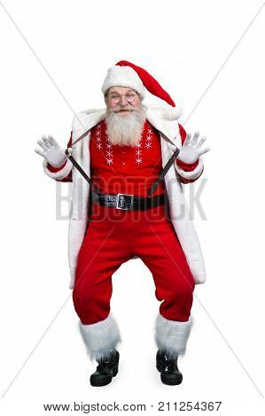 Funny Santa Claus holding his suspenders. Bearded Santa Claus having fun isolated on white background.