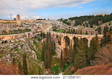 Gravina in Puglia, Bari, Italy: landscape of the the deep ravine with the ancient aqueduct bridge, the old rock church Madonna della Stella and the cave houses carved into the tufa rock