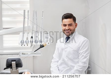 Young cheerful male professional dentist smiling to the camera joyfully sitting at his office copyspace dental oral examination checkup professionalism occupation medicine doctor.