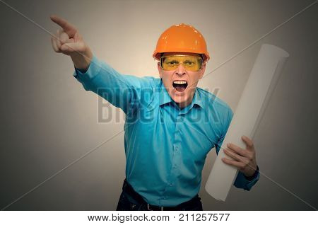 An angry engineer worker with project drawings in his hand yells and screams at someone and showing a poorly executed job with his index finger. Bad job.