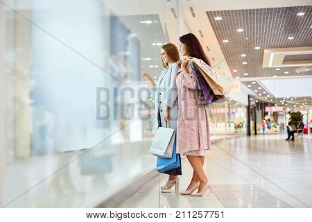 Full length portrait of two beautiful girls  in shopping center looking at window displays of store and smiling, choosing clothes