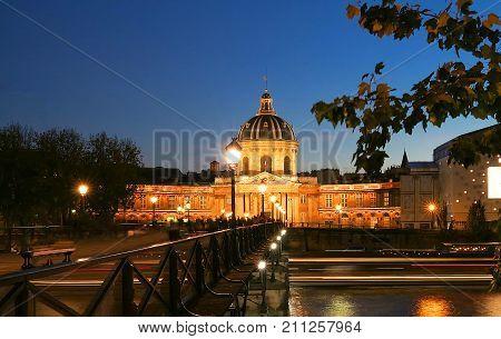 The Institut de France building and bridge of Arts at night, Paris, France.