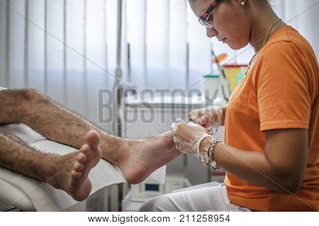 podiatry doctor curing a young patient feet