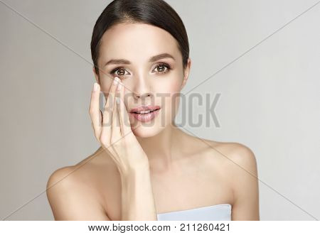 Beautiful Young Woman with Clean Fresh Skin . Facial  treatment   . Cosmetology , beauty  and spa .  Skin care . Beauty skin famale  face . Eye cream or the woman wears the contact lenses  .