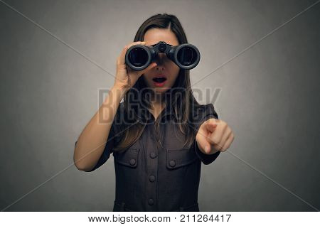 Young woman looking through binoculars with her wide open mouth and pointing ahead with her index finger. Find and search. Find something interesting.