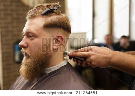 Barber styling beard with trimmer at barbershop, closeup of client's head. Male Barbershop