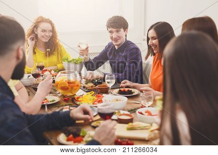 Friends meeting. Group of happy people talking and eating healthy meals at party dinner table in cafe, restaurant. Young company celebrate with alcohol and food at wooden table indoors.