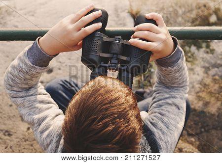 Little caucasian boy watching searching for looking gazing by binoculars top view