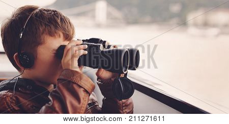 Little caucasian boy with headphones listening audio guided tour on Danube watching searching for gazing looking by binoculars Budapest Hungary