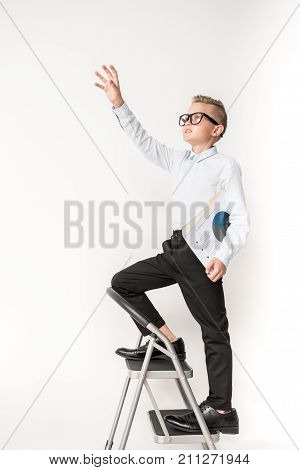 Reaching goal concept. Full length of confident little smart boy in glasses is climb the stepladder in adult shoes and holding important papers while rising hand up. Copy space. Isolated background