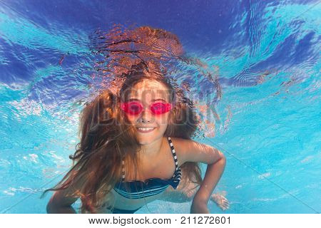 Portrait of happy preteen girl in pink goggles swimming underwater and looking to camera