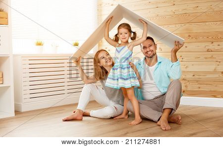 concept housing a young family. Mother father and child in new house with a roof