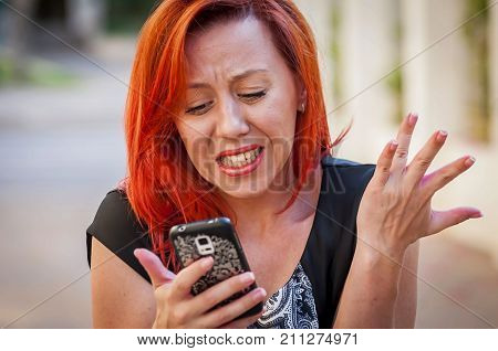 Cute Caucasian girl with red hair holding cellular phone in her hands with an upset, irritated look. Phone spam concept, bad news illustration, phone not working, technical bug, phone bullying.