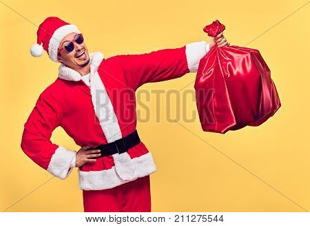 Santa Claus. Young Happy Santa Man. Christmas Santa sack bag Presents gifts. Portrait Handsome Fashion guy Having Fun Smiling. New Year. Emotional Confident Santa Claus. Stylish Colorful Xmas Holiday