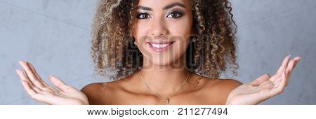 Beautiful woman portrait. Hands up and smiling beauty fashion style mulatto curly hair with white locks eyes look into the camera