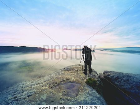 Professional On Cliff. Nature Photographer Takes Photos With Mirror Camera On Peak Of Rock. Dreamy F