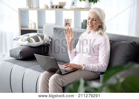 Portrait of happy senior woman using laptop for online communication. She is waving arm to gadget and laughing. Woman is sitting on couch in living room