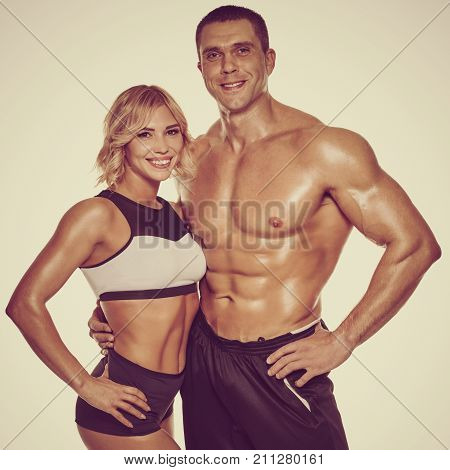 Young sporty woman posing with her personal fitness trainer. image with vintage toning