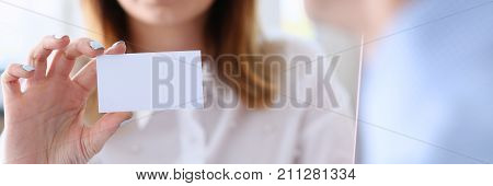 Smiling business woman in suit hold in hand blank calling card closeup. White collar partners company name exchange executive or ceo introducing at conference product consultant sales clerk concept