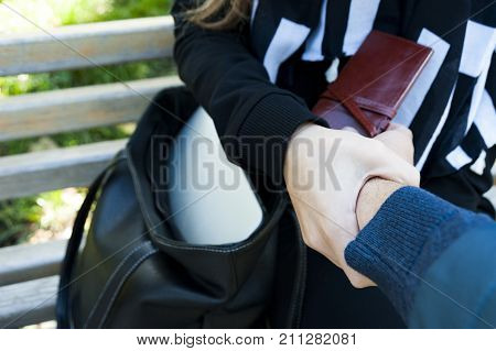 The female human hand stops the robber who steals a wallet from a bag. Stop a robber concept.