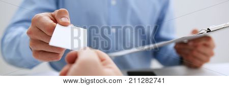 Male hand in suit give blank calling card to female visitor closeup. White collar partners company name exchange executive or ceo introducing at conference product consultant sale clerk concept
